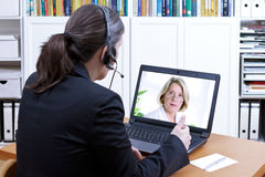 Female accountant headset online meeting. Female tax adviser with headset in front of a laptop giving online financial advice to an elderly client, video call Stock Photo
