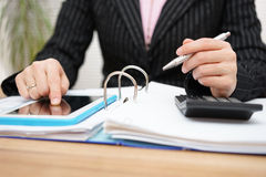 Female accountant using assistance on tablet pc to complete work Royalty Free Stock Photography