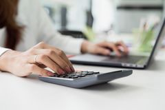 female accountant using calculator and typing on laptop. stock photography