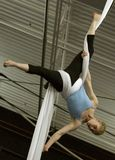 A female acrobat hangs upside down by wrapping aerial silks around her waist and legs. stock photos