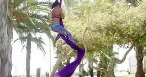 Female acrobat working outdoors on silk ribbons stock video