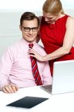 Female adjusting her co-workers tie Royalty Free Stock Image