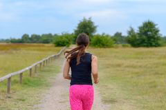 Female adult jogger running away from camera. Along unpaved road in a close up view royalty free stock image