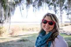 Female adult portrait of a blonde Caucasian woman underneath Spanish Moss in Beaufort, South Carolina. Wearing red sunglasses and stylish outfit royalty free stock image