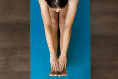 Female adult stretching on a yoga mat in class royalty free stock photo