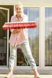 Woman using broom to clean up backyard patio. Female adult young woman using big broom to clean up backyard patio Stock Photo