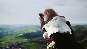 Female Adventurer looking down at landscape stock footage