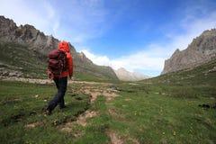 Woman hiking on high altitude mountain. Female adventurer walking on high altitude mountain Stock Photo