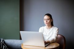 Female advertiser listening to music via headphones and keyboarding promotional text on netbook stock image