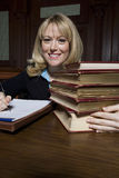 Female Advocate With Law Books. Portrait of a happy female advocate with stack of law books in courtroom Royalty Free Stock Photography