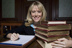 Female Advocate With Law Books. Portrait of a happy female lawyer with stack of law books writing notes in courtroom Stock Photography