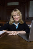 Female Advocate Sitting In Courtroom. Portrait of a happy female advocate sitting in courtroom Royalty Free Stock Photo