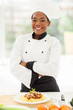 Female african chef. Pretty female african chef with arms crossed standing in hotel kitchen royalty free stock image