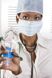 Female african doctor. Young attractive african doctor with face mask holding mask up to the patient Stock Photo