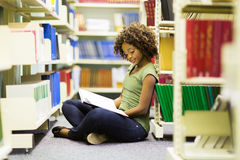 Female african student. Female african american student sitting on the floor reading a book in library Stock Image