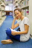 Female african student library. Gorgeous female african student sitting on library floor and reading Stock Image