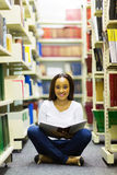Female african student library. Female african student sitting on library floor and reading Royalty Free Stock Photo