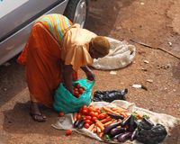 Female African Vegetable Vendor. KAMPALA, UGANDA - SEPTEMBER 28, 2012.  An African woman bends over to organize her for sale vegetables in the taxi park in Stock Photos