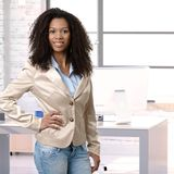 Female afro officeworker posing at office desk Stock Photo