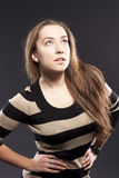 Female against a dark background. striped jacket. Woman looking up. studio on dark Stock Photography