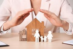 Free Female Agent Covering Wooden Houses And Family At Table. Home Insurance Royalty Free Stock Photos - 141105478