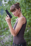 Female agent with gun. Young female agent with a gun outdoors Royalty Free Stock Photo