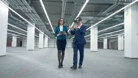 Female agent is showing empty office premises to a man in VR-glasses. 4K stock footage