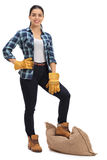 Female agricultural worker with burlap sack under her foot Royalty Free Stock Images