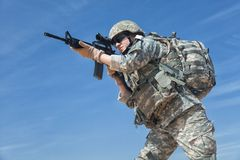 Female airborne. Portrait of United states airborne infantry female with arms, camo uniforms dress. Combat helmet, backpack rucksack, low angle stock photography