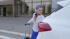 Female airport staff goes to white car with travel suitcase on background airport. Building stock footage