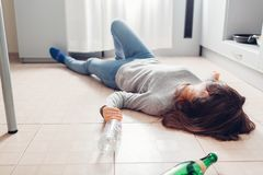 Female alcohol addiction. Young woman sleeping on kitchen floor after party surrounded with wine bottles. Alcoholism royalty free stock photo