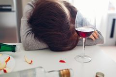 Female alcohol addiction. Young woman sleeping on kitchen table surrounded with wine bottles. Alcoholism royalty free stock images