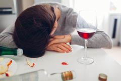 Female alcohol addiction. Young woman sleeping on kitchen table surrounded with wine bottles. Alcoholism royalty free stock photos
