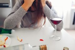Female alcohol addiction. Young woman woke up on kitchen after party surrounded with wine bottles. Hangover royalty free stock image