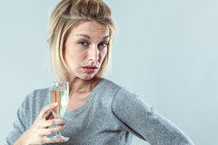 Female alcoholism for depressed young blond woman. Female alcoholism - depressed young blond woman drinking a flute of bubbly wine with alcohol side effects royalty free stock photos