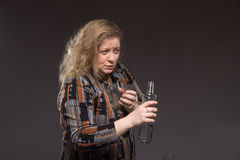 Female alcoholism. Woman aged one drinks vodka from a bottle and Stock Photo