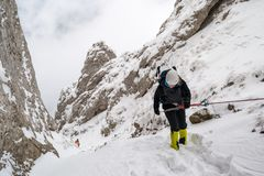 Female alpinist rappeling into a steep canyon filled with snow, during a Winter hiking trip, in Piatra Craiului mountains. Part of the Carpathian mountains, in stock images