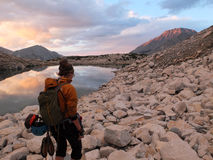 Female alpinist in the Sierra Nevada at sunset. Mountain climber on the way back from Bear Creek Spire, California, USA Stock Image