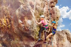 Two alpinists climbs the rock with harnesses royalty free stock photography