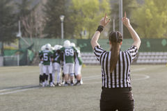 Female American football referee and blurred players in the back Stock Photography