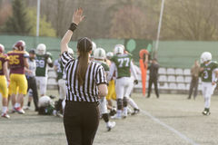 Female American football referee giving signals and blurred play Stock Photo