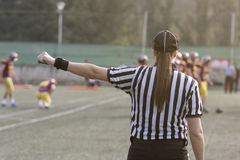 Female American football referee giving signals and blurred play Royalty Free Stock Photos