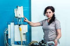Female anesthesiologist doctor standing in front of the ventilat. Young female anesthesiologist preparing for surgical intervention in the operating room, in Stock Image