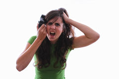 Female angry with a console game. Caucasian female holding game controller against her head with her other hand in her hair screaming with anger at a console Stock Photos