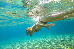 Female apnea underwater. Female apnea bikini swims in crystal sea. Underwater background of a woman snorkeling and doing skin diving. Watersport activity in Stock Photography