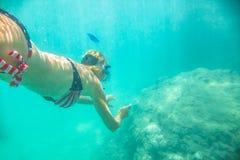 Female apnea underwater. Woman snorkeler swims in tropical sea with american flag bikini. Underwater scene of a female apnea and doing skin diving. Watersport Stock Image