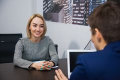 Female applicant during job interview with male boss. Female applicant during job interview with male boss reading her resume, businessman listen to candidate royalty free stock image