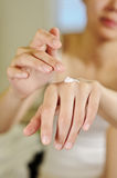 Female applying cream to her hands Stock Image