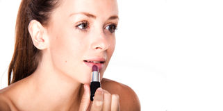 Female applying a lipstick Stock Photos