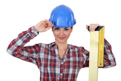 Female apprentice. Looking pleased with ruler and hard hat stock image